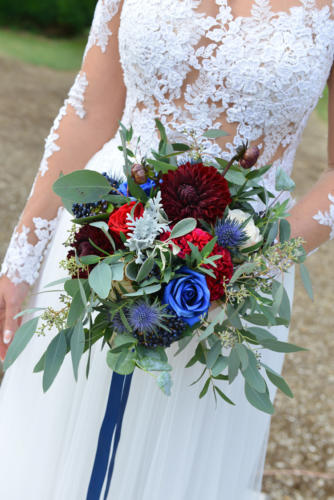 Bouquet de mariée rond déstructuré dans les tons bleus et rouges en roses, dahlias et feuilles d'eucalyptus
