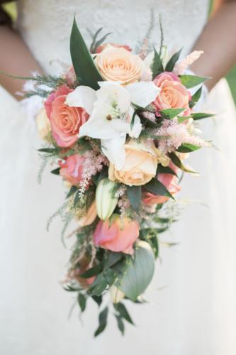Bouquet de mariée retombant dans les tons blancs, pêches et corails en roses, lys et astilbe aromatique fleuriste mariage