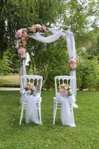 Arche drapée et fleurie avec rappel sur les chaises des mariés aromatique fleuriste mariage