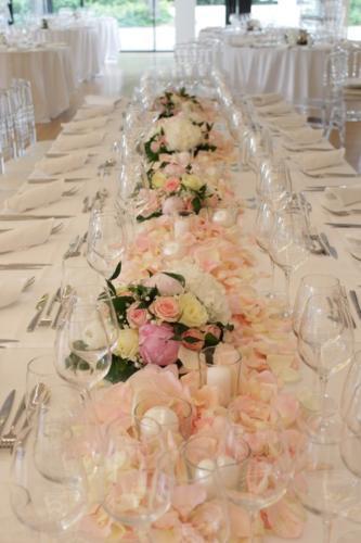 Table d'honneur fleurie et couverte de bougies et pétales aromatique fleuriste mariage