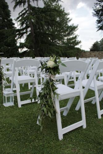 Rose blanche et feuillages sur les chaises de cérémonie aromatique fleuriste mariage