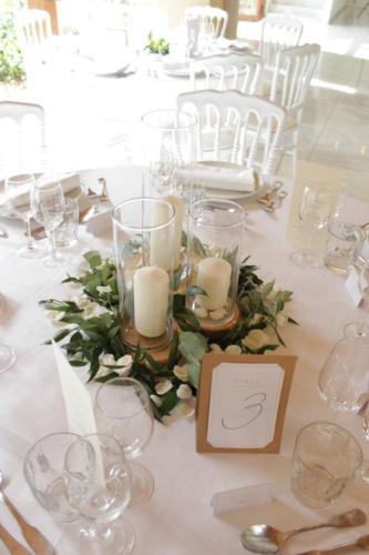 Centre de table mêlant rondins, feuillages et bougies aromatique fleuriste mariage