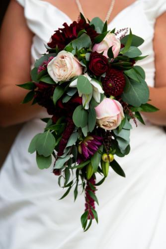 Bouquet de mariée retombant dans les tons roses et bordeaux en dahlias, amaranthe et roses aromatique fleuriste mariage