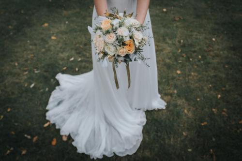 Bouquet de mariée rond champêtre en roses blanches crèmes et pêches et feuillages dorés aromatique fleuriste mariage