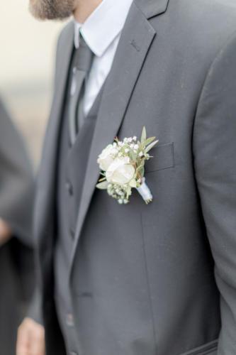Boutonnière élégante en roses blanches et feuillages aromatique fleuriste mariage