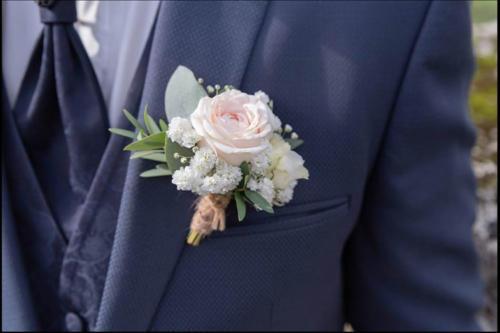 Boutonnière romantique en boutons de roses, gypsophile et feuillages légers aromatique fleuriste mariage