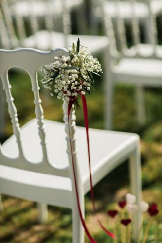 Bouquet de gypsophile et olivier sur les chaises de cérémonie aromatique fleuriste mariage