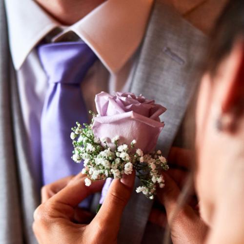 Une rose mauve en boutonnière aromatique fleuriste mariage
